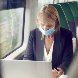 Businesswoman On Train Working On Laptop Wearing PPE Face Mask During Health Pandemic
